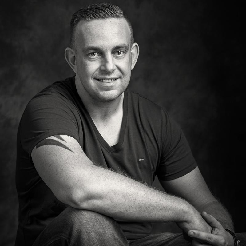 En mand sidder på gulvet og smiler