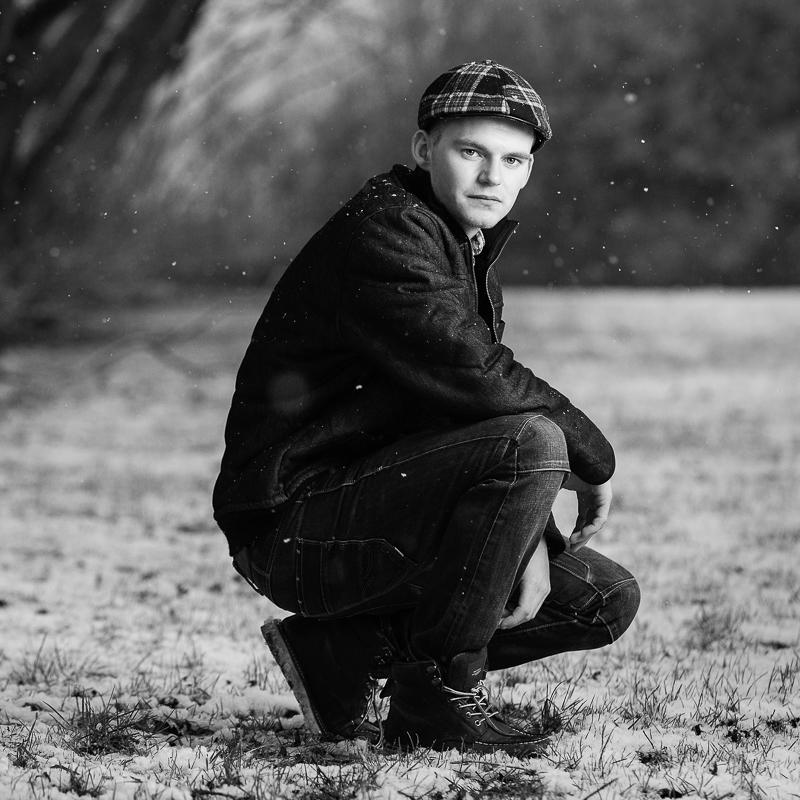 Maskulin fotosession: En mand er fotograferet på græs i snevejr