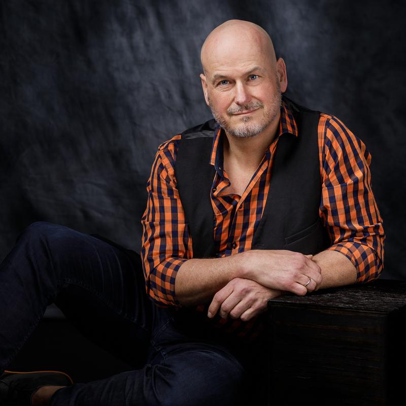 Maskulin fotosession: En mand sidder med orange skjorte foran et mørkt tæppe